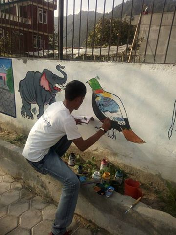 One of our volunteer Ram Bahadur busy on painting & decorating school's wall.